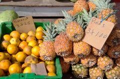 Abacaxis e laranjas para a venda no carrinho de fruta Imagem de Stock Royalty Free