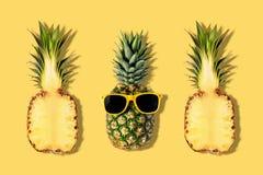 Abacaxis frescos com os ?culos de sol no fundo amarelo Conceito criativo do suumer foto de stock royalty free