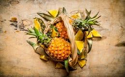 Abacaxis frescos na cesta Na tabela de madeira Fotografia de Stock