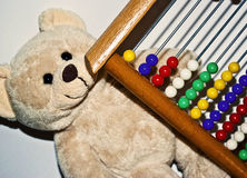 Abacus. An all colored abacus for children to start counting and a teddy bear Royalty Free Stock Images
