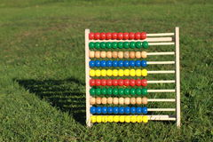 Abacus. Colorful abacus on the grass with shadow behind stock photography
