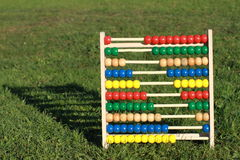 Abacus. Colorful abacus on the grass with shadow behind royalty free stock images