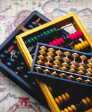 Abacus. Three Abacus on an out of focus antique map Stock Photos