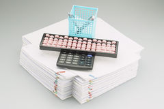 Abacus and calculator with blue pen box placed on paperwork Royalty Free Stock Photo