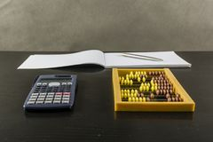 Abacus and calculator on a wooden desk. Abacus and calculator on a wooden dark desk Royalty Free Stock Photography