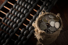 Abacus with coins in gunny sack. Royalty Free Stock Photography