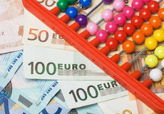 Abacus and european money. Abacus beads with euro, european money as background Royalty Free Stock Photo
