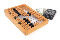 Abacus. Financial concept. Old wooden abacus, money (dollars and euros) and a calculator nearby isolated on white Royalty Free Stock Photography