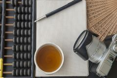 Abacus, notebook, camera and tea placed on the table stock photos