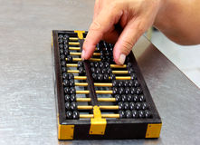 Abacus with old man's hand Royalty Free Stock Image