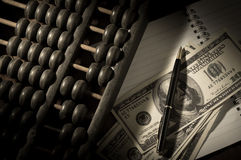 Abacus with pen and money on book. Royalty Free Stock Photo