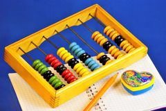 Abacus for teaching children to count. Abacus device for performing arithmetic calculations, notebook for records, colored pencil stock photos