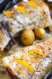 Abadejos cocidos con las rebanadas del limón y las pequeñas patatas Foto de archivo libre de regalías