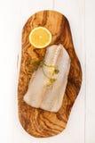 Abadejos crudos con eneldo y el limón en un tablero de madera Fotografía de archivo libre de regalías