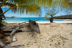 Abadoned boat in sandy beach in Antsiranana bay Madagascar. Abadoned traditional aboriginal Malagasy wooden hand made fisherman dugout catamaran boat - canoe on Royalty Free Stock Image