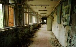 Abadoned skolakorridor med öppna fönster på Tjernobyl stadszon Royaltyfria Foton