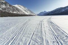 Abaissez le lac Multinsky sous la neige, un jour ensoleillé Photographie stock libre de droits