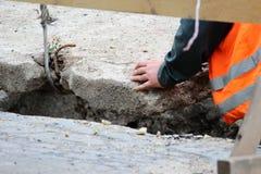 abaixando a laje de cimento e a criação da proteção do canal das tubulações de água da danificação durante o trabalho do reparo foto de stock