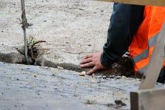 abaixando a laje de cimento e a criação da proteção do canal das tubulações de água da danificação durante o trabalho do reparo fotos de stock