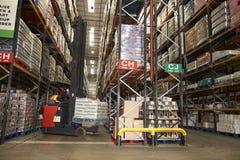Abaixando o estoque em um armazém de distribuição usando o caminhão do corredor fotos de stock