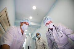Abaixo da opinião os cirurgiões que guardam instrumentos médicos nas mãos e que olham o paciente imagens de stock royalty free
