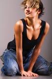 Abajo arrodillada mujer de moda atractiva Imagen de archivo