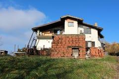 Abajo batida casa suburbana con desperdicios y la pared de ladrillo en frente Fotos de archivo libres de regalías