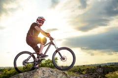Abajo ciclista profesional de la colina que descansa con la bici en la roca en la puesta del sol Deporte extremo Foto de archivo