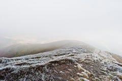 Abajo de la montaña en mañana congelada y la niebla Imagen de archivo
