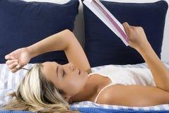 Abajo en cama con el libro Fotografía de archivo