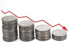 Abajo flecha sobre pilas de monedas Imagenes de archivo