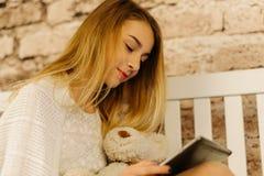 Abajo la opinión el adolescente joven ussing la tableta y que sostiene el oso de peluche Fotos de archivo