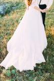 Abajo la pieza del vestido de boda largo de la novia y del novio que se colocan en la hierba verde cubierta con las flores Fotos de archivo