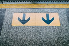 Abajo la señal de la flecha, se guarda de los pasajeros que dejan el tren Fotos de archivo libres de regalías