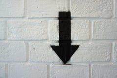 Abajo muestra de la flecha en la pared de ladrillo blanca Imagen de archivo