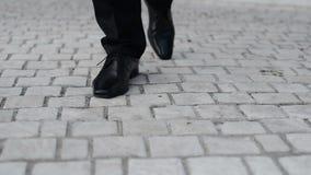 Abajo opinión sobre el novio que camina en el pavimento almacen de video
