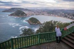Abajo opinión sobre la mujer turística joven que admira la naturaleza hermosa de la bahía del concha del la encendido de la costa Fotografía de archivo libre de regalías