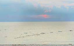 Abajo sol en horizonte de mar Imagen de archivo libre de regalías