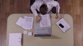 Abajo tiró de hombre de negocios en su lugar de trabajo que miraba a través de los documentos metrajes