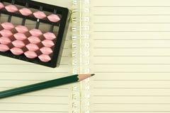 Abakus gesetzt auf Notizbuch mit Bleistift Stockfoto