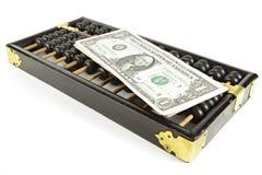 Abakus mit Dollar auf Isolatweiß Stockfotografie