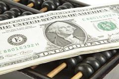 Abakus mit Dollar auf Isolatweiß Lizenzfreies Stockfoto