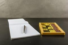 Abakus mit einem Stift und einem Notizbuch Lizenzfreie Stockfotos