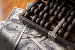 Abakus mit Geld Lizenzfreie Stockfotografie