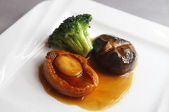 Abalone. With sauce, mushroom and broccoli in the dish Royalty Free Stock Photography