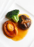 Abalone. With sauce, mushroom and broccoli in the dish Stock Images