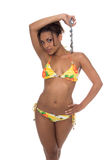 Abalone Bikini. Beautiful African American woman in a yellow tropical bikini holding a blue Abalone shell necklace over her head Royalty Free Stock Image