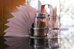 Abanador de vidro da pimenta e de sal, palitos e guardanapo na tabela no café na frente da janela foto de stock royalty free
