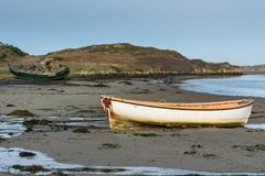 Row boat out of water. Abandon Fishing boat and row boat  on the sand at low tide Stock Photos