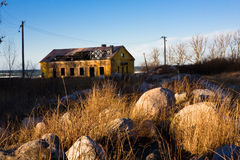 Abandon house behind rocks. An old yellow soviet time abandoned house behind big rocks. Sea is behind the house Stock Images